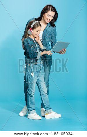 Happy Mother And Daughter In Headphones Using Digital Tablet In Studio On Blue