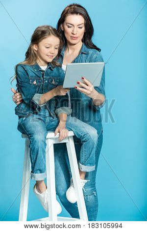 Happy Mother And Daughter Using Digital Tablet In Studio On Blue