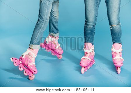 low section of mother and daughter in roller skates in studio on blue