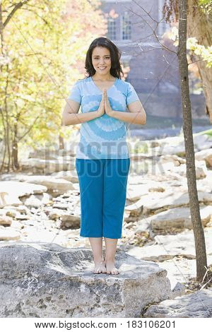 Mixed race woman doing yoga in park