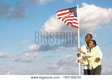 Multi-ethnic couple holding American flag