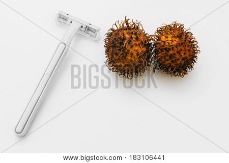 Shaving intimate zones, hygiene. Man balls, unwanted pubic hair. Two hairy eggs with razor on white background, flat lay.