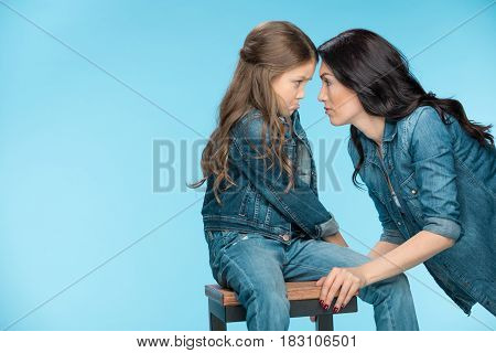 Offended Daughter And Mother Looking At Each Other In Studio On Blue