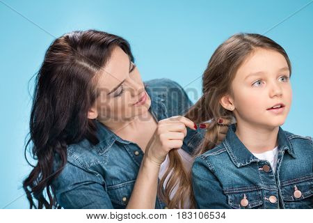Portrait Of Happy Mother Braiding Daughter's Hair In Studio On Blue
