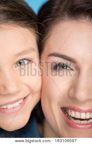 Headshot Portrait Of Happy Mother And Daughter Hugging In Studio On Blue