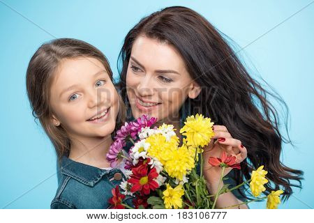 Happy Mother And Daughter Hugging And Holding Flowers In Studio On Blue, Happy Mothers Day