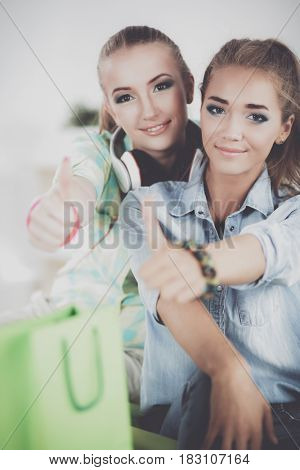Two young women sitting with shopping bag at home, showing ok