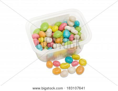 Candies made of the the raisins covered by varicolored sugar glaze and called sea pebbles in the small transparent plastic container and several candies separately beside on a light background