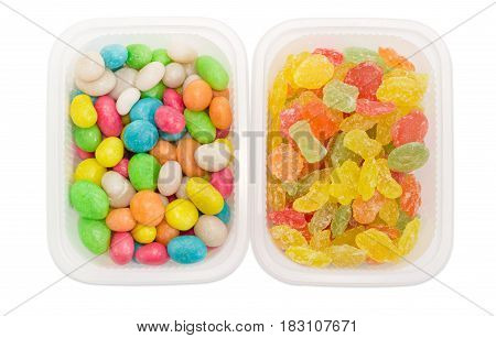 Top view of the varicolored sugar candies and candies made of the raisins with hard sugar shells and called sea pebbles in two small plastic containers closeup on a light background