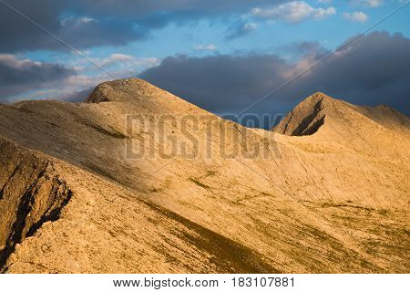 Closeup view of peaks Kutelo and Banski suhodol joined by the Koncheto Saddle in Pirin mountains under a stormy cloudy sky with a shaft of sunlight illuminating the range Bulgaria