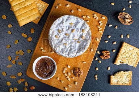 Camembert On Wooden Cutting Board With Nuts