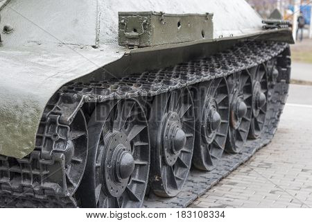 the front part of the green caterpillar of the tank standing on the ground with the wheels close-up