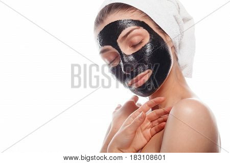 Young woman with black cleansing mask on face and towel on head posing sensually on white background.