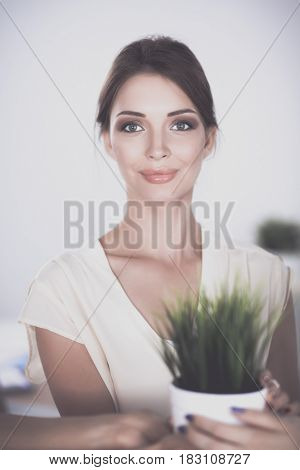 Beautiful woman holding pot with a plant