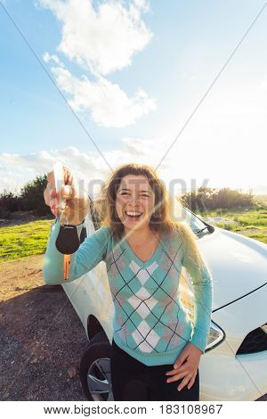 auto business, car sale, consumerism and people concept - happy woman holding new car key outdoor.