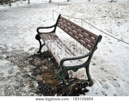 Brown bench chair with dirty mud in snow storm Iceland