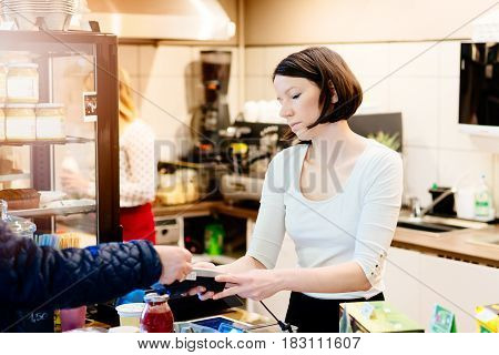 Customer Paying With Credit Card In Small Shop
