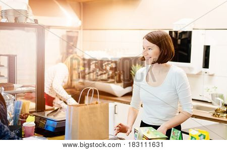 Satisfied female owner of a local store stands smiling behind the counter of her small business