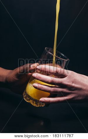 Orange juice pour in glass hold by unrecognizable white woman and black man hands, on black background. Fresh drink, healthy lifestyle, international relationship concept.