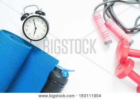 Flat lay of sport yoga equipments and alarm clock on white background
