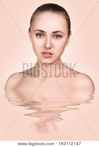 Young beautiful woman with reflection on water surface