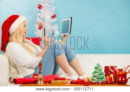 Christmas time concept. Young woman teen girl with tablet pc laptop and credit card on sofa at home doing online shopping buying browsing for gifts having fun