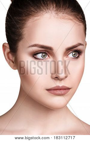 Beautiful face of young woman with clean skin over white background.
