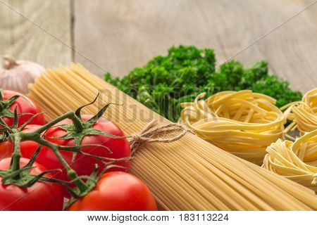 spaghetti and tagliatelle with ingredients for cooking pasta. Curly parsley garlic tomatoes on a wooden table.
