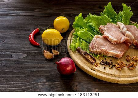 Slices of raw meat. Pork escalope on a wooden board. With the ingredients for cooking.