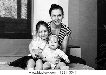 Happy loving family. Mother and her daughters hugging and posing.
