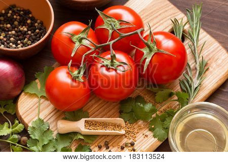Ingredients for cooking sauce. Sprig of tomatoes parsley garlic mushrooms pepper pots mustard seeds.