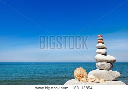 concept of peace and harmony. A pyramid of white stones and shells on background of summer sea. copy space
