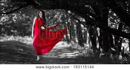 Sexy fashion model with naked walking in a fantastical forest. Photo of seductive nude woman in full length in luxury long red dress posing against bokeh trees background. Multi-racial Asian Caucasian girl. Fashionable toning. Creative computer colors.