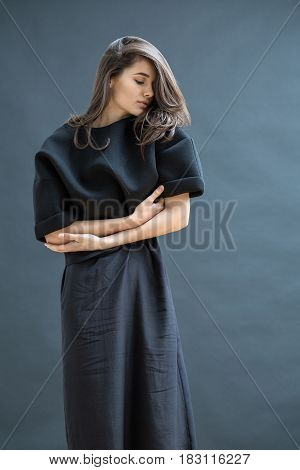 Delightful girl in a dark dress is posing in the studio on the isolated background. She holds her right hand on the left arm and presses them to the body. Her head turned to the left. Vertical.