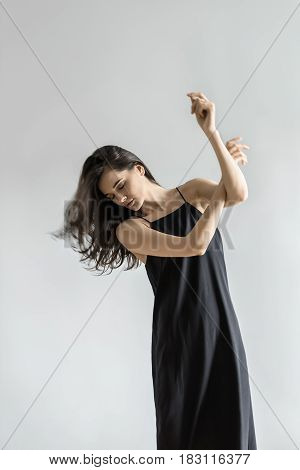 Brunette girl with closed eyes and windy hair in a dark dress is posing in the studio on the gray background. Her arms are crossed and left hand stretches above. Hair partially blurred in the motion.