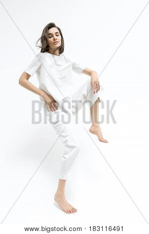 Sensual barefoot girl with windy hair is posing in the studio on the white background. She wears a white T-shirt and pants. Woman holds right hand on the hip, left hand is on the knee of raised leg.