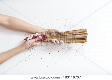 Woman's hands in powder are holding a bunch of incense sticks on the white background in the studio. Sticks colored in red-brown. Closeup. Horizontal.
