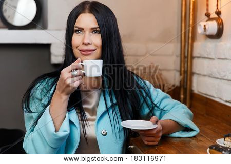 Brunette with cup of coffee resting in cafe