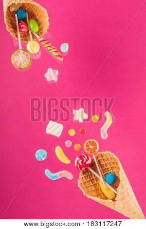 Waffle Cones With Different Delicious Jelly Candies And Lollipops On Pink