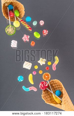 Waffle Cones With Different Delicious Jelly Candies And Lollipops On Grey