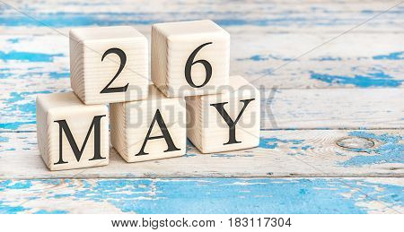 May 26th. Wooden cubes with date of 26 May on old blue wooden background.