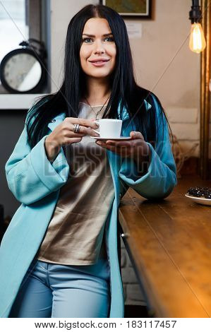 Young brunette resting with coffee in cafe