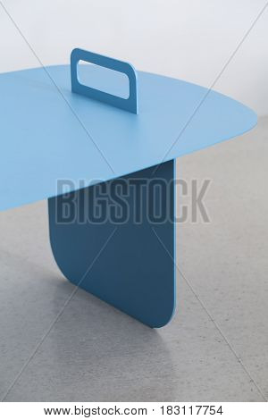 Blue metal stand on the gray surface on the blurry background. Closeup low aperture photo. Indoors. Vertical.