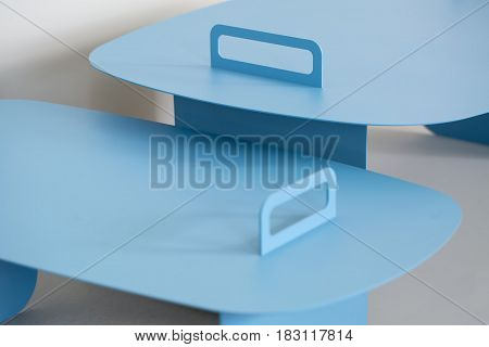 Couple of metal cyan stands on the gray background. Closeup low aperture photo. Indoors. Horizontal.