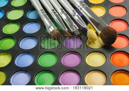 Three Brushes on the palette of eye shadows - orange, blue, yellow, green. purple, red colors