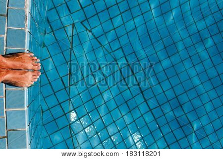 Man stands at edge of pool with clear water