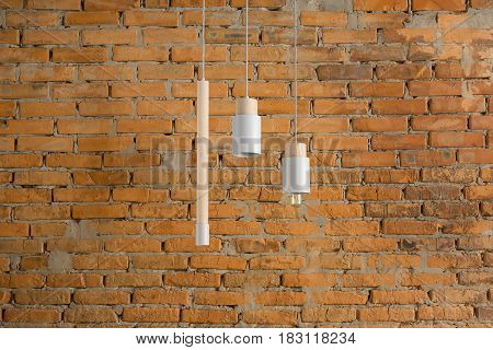 Three gray lamps with light wooden parts are hanging on the cables on the brick wall background. One lamp has an edison bulb. Closeup. Horizontal.