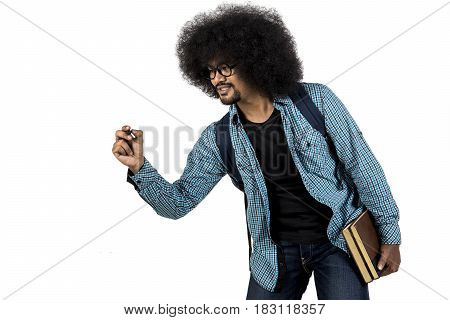 Afro man writing on copy space while holding book in his hand isolated on white background