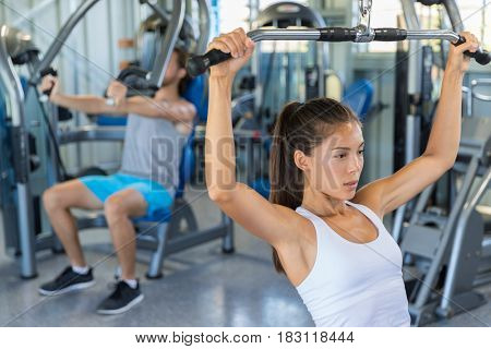 Fitness girl working out shoulders and upper back at lat pulldown machine, strength training at gym.