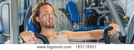 Portrait of fitness man working out chest muscles with vertical bench press machine. Difficult exercise at gym. Banner panoramic crop ad.
